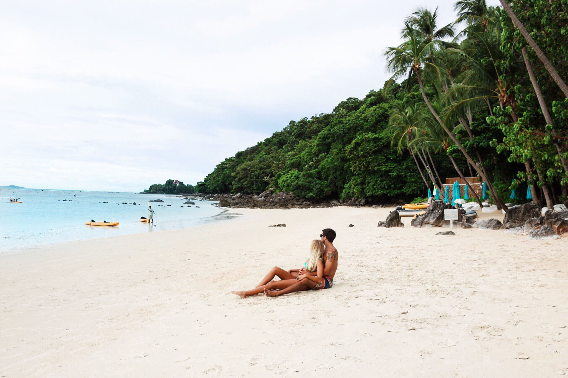 couples coordinates laying on beach at four seasons koh samui