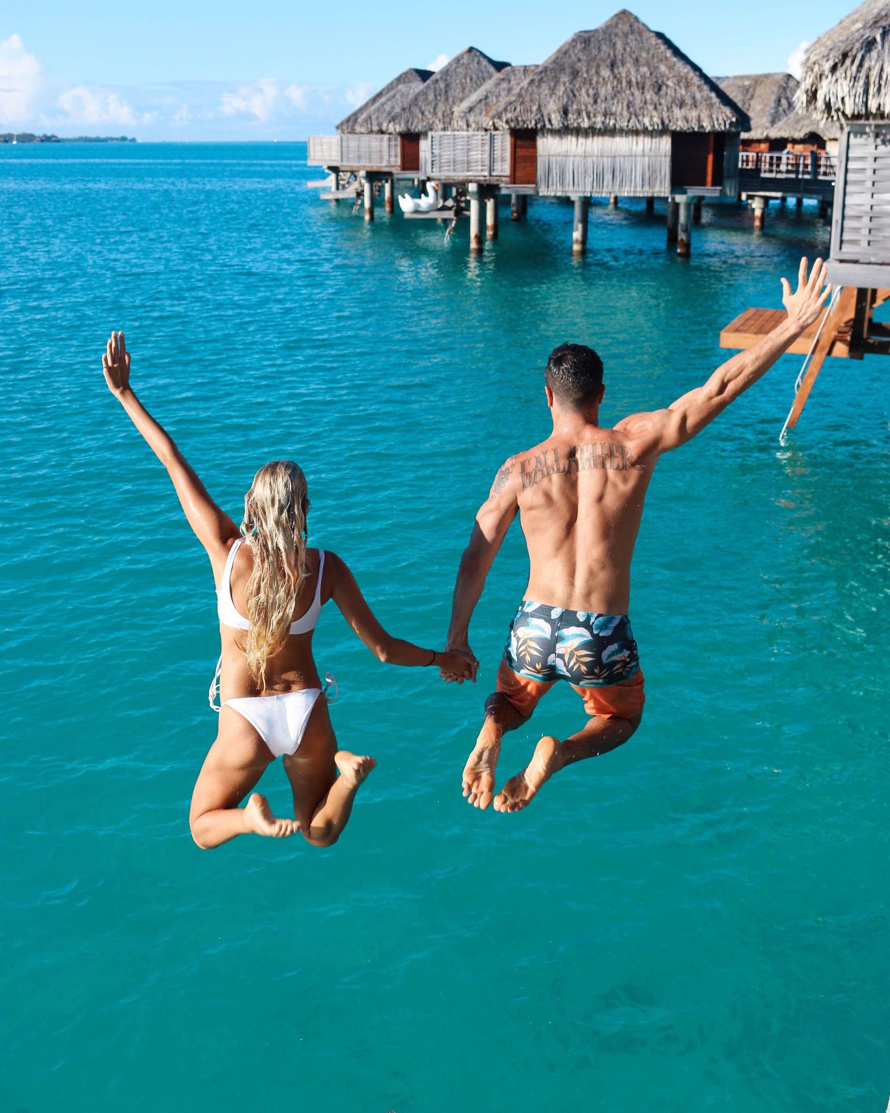 couples coordinates bora bora honeymoon guide michael and alex juping off bungalow four seasons bora bora