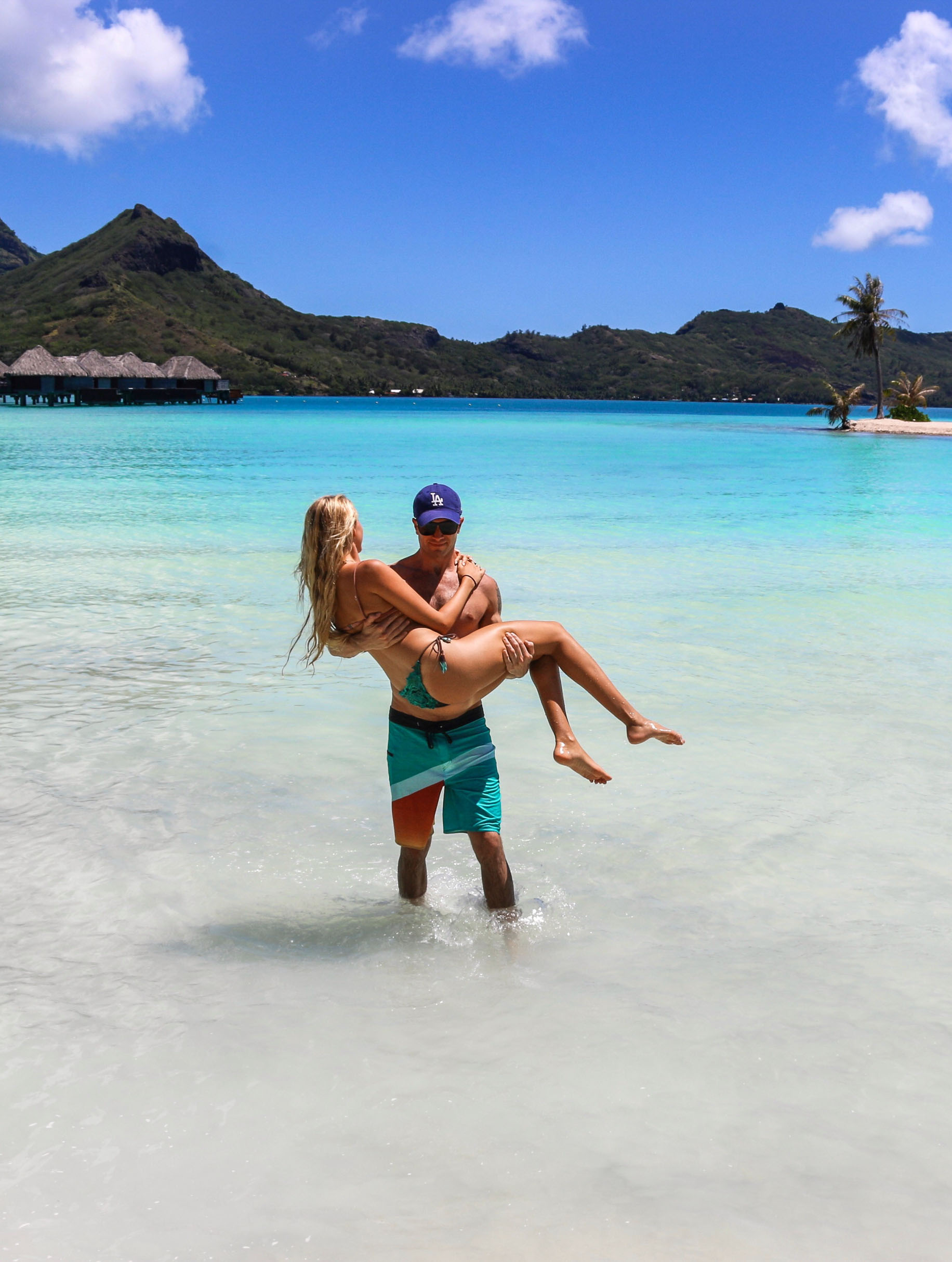 couples coordinates bora bora honeymoon guide michael carrying alex in ocean by motu