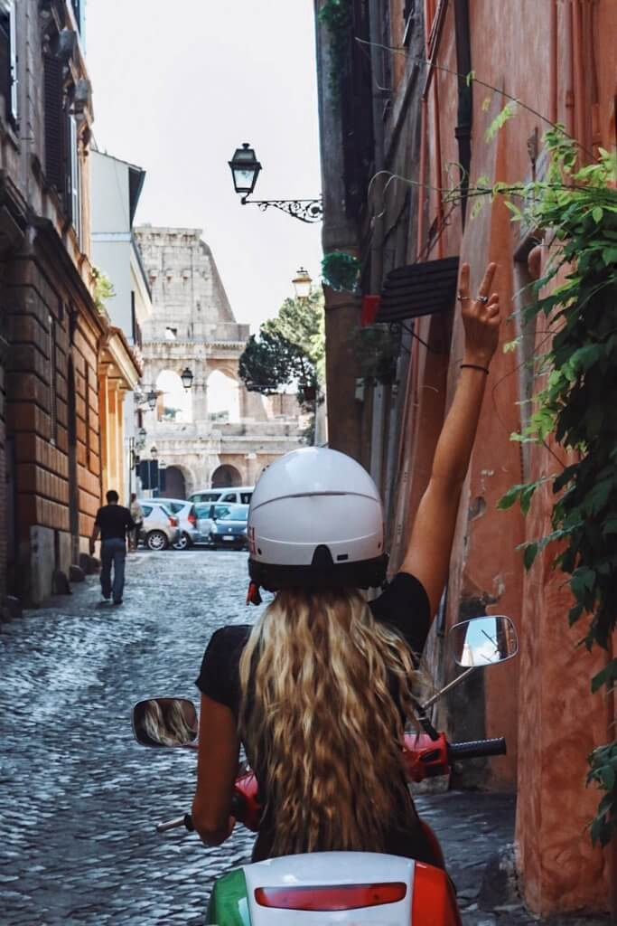 couples coordinates alex riding a vespa near the colosseum in rome italy