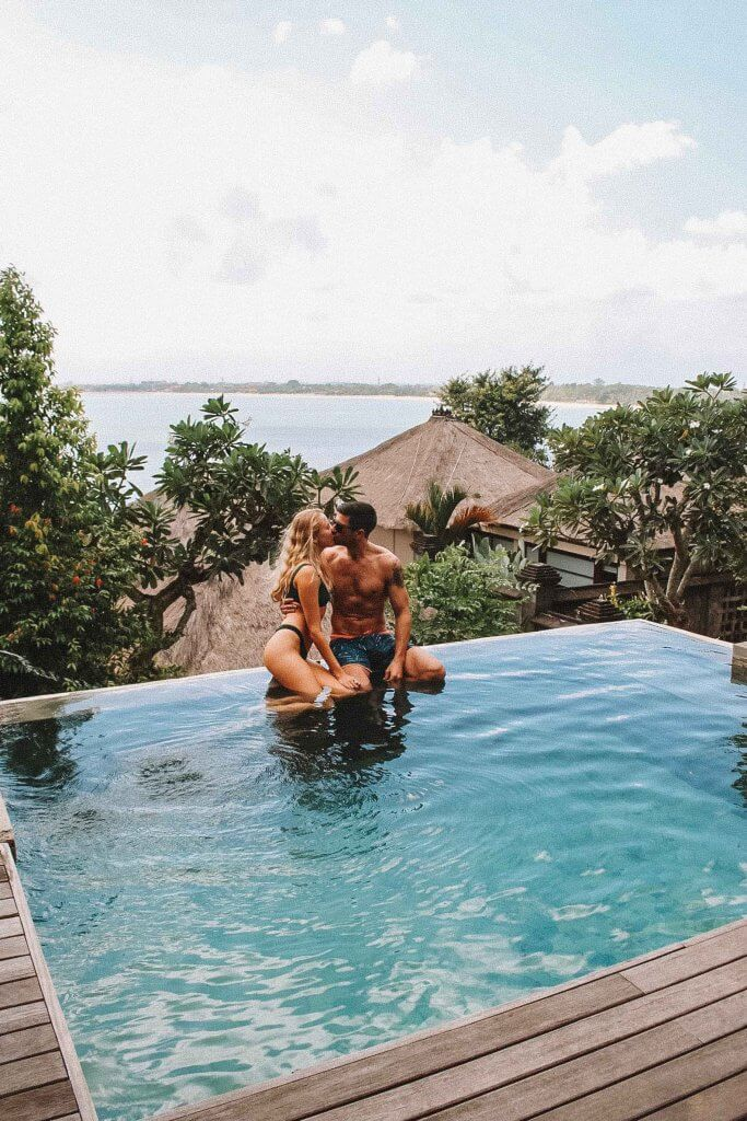 couples coordinates staying at four seasons bali four seasons jimbaran pool kiss