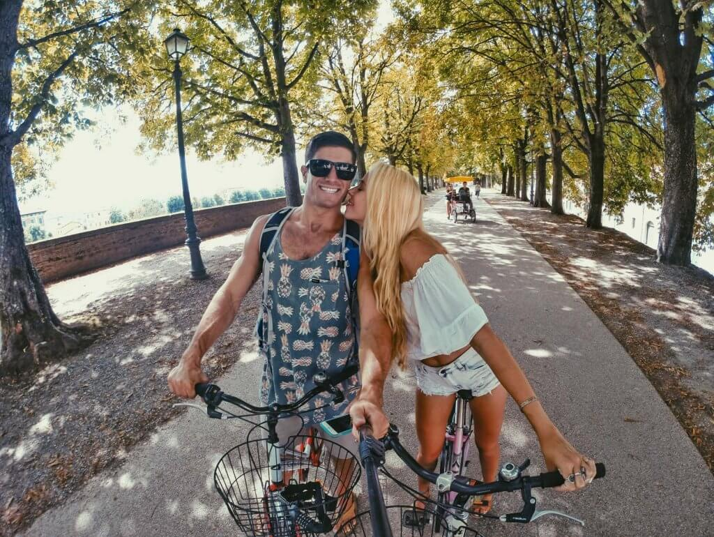 couples coordinates riding bikes in lucca italy small town destinations for couples
